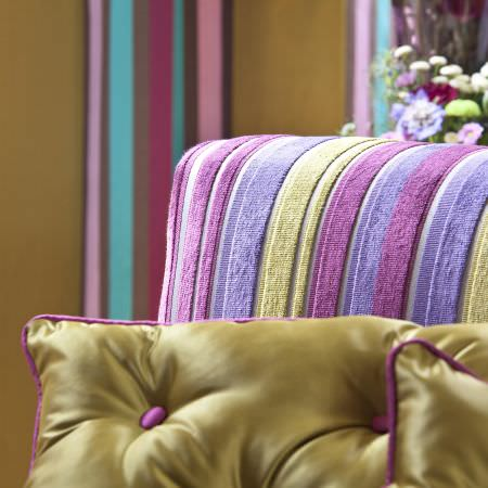 Prestigious Textiles -  Sophistication Fabric Collection - Close-up photo of plain green cushions with pink buttons and edges made of reflective fabric, and a pink and green striped upholstery