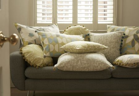Prestigious Textiles -  South Bank Fabric Collection - A collection of decorative cushions in different shapes and featuring different designs on plain grey sofa