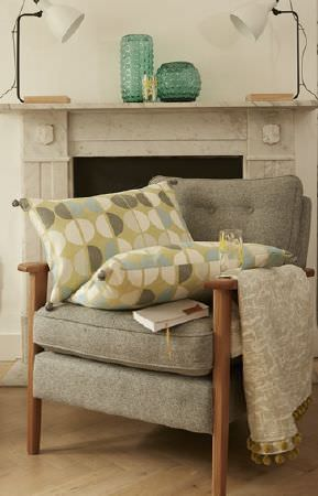 Prestigious Textiles -  South Bank Fabric Collection - Light grey armchair and lime green cushions with matching colourful pattern and plain beige fabric with fringes