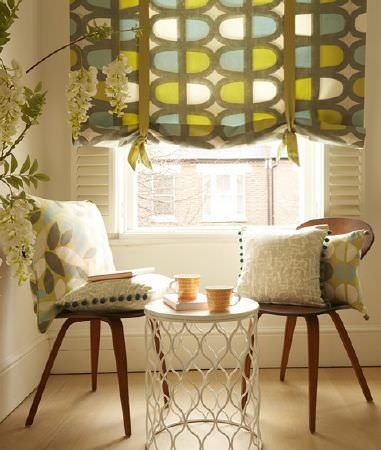 Prestigious Textiles -  South Bank Fabric Collection - Matching colourful pattern on tied roman blinds and cushions and a set of plain beige cushions