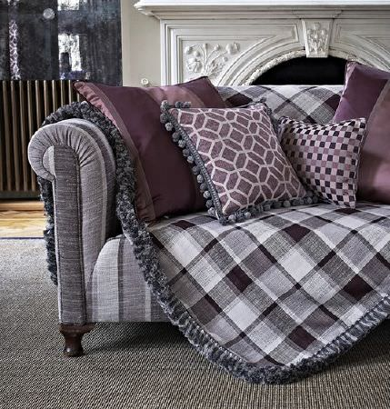 Prestigious Textiles -  Spectrum Fabric Collection - A sofa striped in shades of grey, a grey checked throw finished with a fringed trim, and four purple patterned cushions