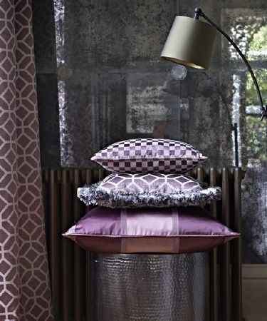 Prestigious Textiles -  Spectrum Fabric Collection - A subtly patterned sheer curtain, a purple geoemtric print curtain, a grey lamp, and 3 grey and purple patterned cushions