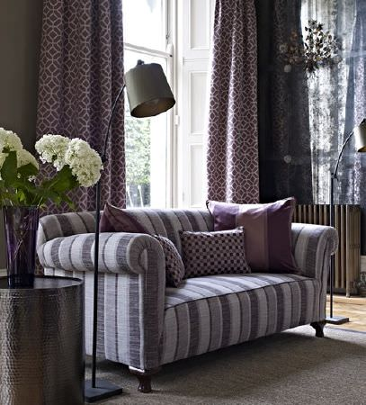 Prestigious Textiles -  Spectrum Fabric Collection - Geometric patterns on purple and grey curtains, a sheer curtain, a grey striped sofa, a grey floor lamp, and cushions