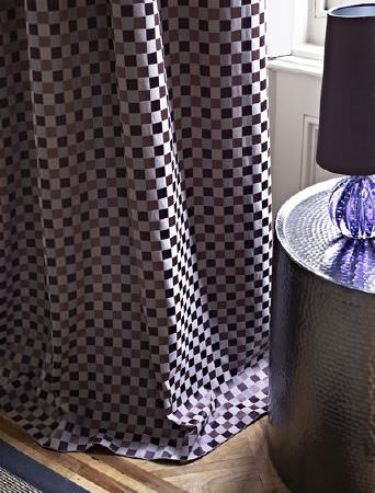 Prestigious Textiles -  Spectrum Fabric Collection - Dark grey, iron grey and silver checkerboard print curtains, with a round silver table and a glass lamp with a grey shade