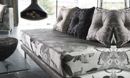 Prestigious Textiles -  Stardom Fabric Collection - modern sofa with large print pattern in cream and grey, honeycomb motif silver cushions