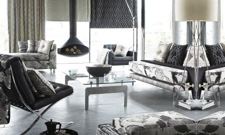 Prestigious Textiles -  Stardom Fabric Collection - Ultra-modern living room with large print leaf motif sofas, silver and black honeycomb patterned cushions, matching Roman blind and curtain