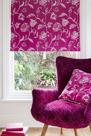 Prestigious Textiles -  Sumatra Fabric Collection - Bright magenta blind and cushion, both with white line drawings of flowers, on a dark magenta patterned armchair
