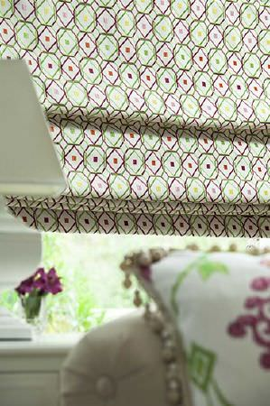 Prestigious Textiles -  Sumatra Fabric Collection - Window blind covered in rounded and angled squares of grass green and magenta, with a patterned cushion with a fringed edge