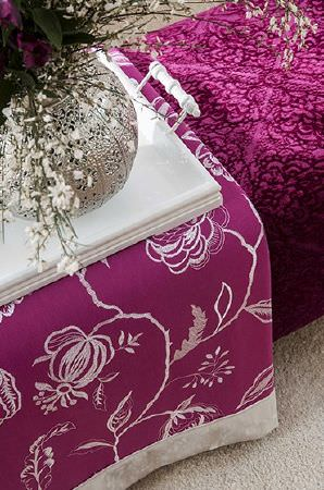Prestigious Textiles -  Sumatra Fabric Collection - Padded magenta box seat style bench with dark pattern, white and magenta floral fabric, topped with a white tray and ornate pewter vase