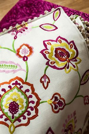 Prestigious Textiles -  Sumatra Fabric Collection - White fabric cushion embroidered with yellow, orange, purple and green flowers and swirls, edged with an off-white bobble fringe