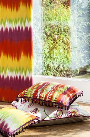 Prestigious Textiles -  Sumatra Fabric Collection - Tie dye effect orange, yellow, green, white and purple fabric, and matching patterned cushions with purple piping and fringing