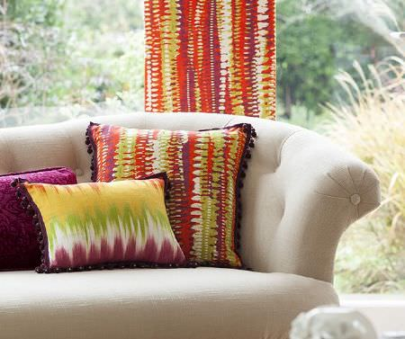 Prestigious Textiles -  Sumatra Fabric Collection - Abstract patterned cushions in bright green, orange, yellow and purple, with purple fringing and a purple cushion, on a cream sofa