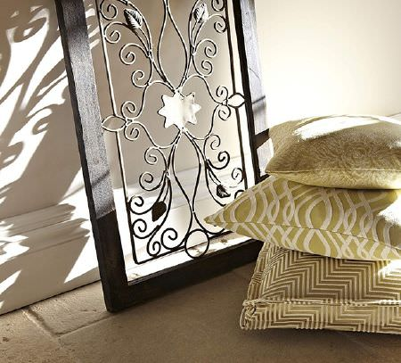 Prestigious Textiles -  Tanomah Fabric Collection - Wrought iron swirl design inside a black frame, with a stack of three embroidered, patterned, white and green-gold cushions