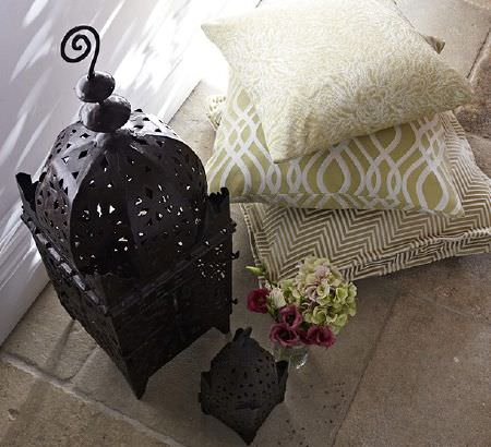 Prestigious Textiles -  Tanomah Fabric Collection - Turkish style black lanterns, with small glass jar vase and three green-gold cushions embroidered with white patterns