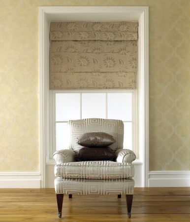 Prestigious Textiles -  Tasman Fabric Collection - Classic white upholstered armchair with a square design pattern and dark grey cushions, in front of a champagne coloured roman blind