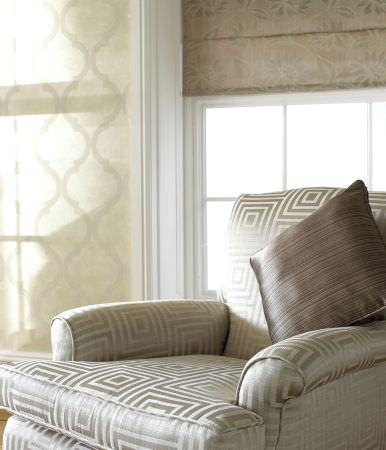 Prestigious Textiles -  Tasman Fabric Collection - A dark gold coloured roman blind with a classic pattern, and a silver upholstered armchair with a square maze pattern with a cushion