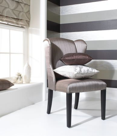 Prestigious Textiles -  Tasman Fabric Collection - A classic chair with reflective grey upholstery and a white and dark brown cushion, and a grey roman blind with wavey lines