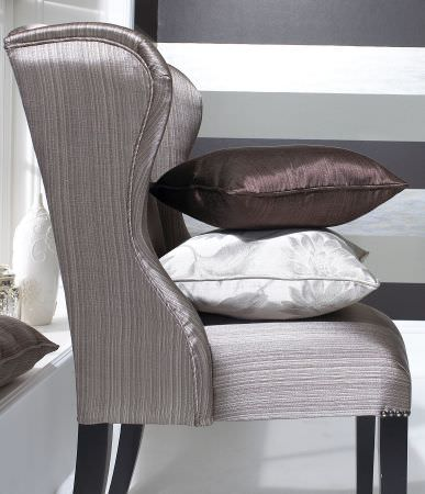 Prestigious Textiles -  Tasman Fabric Collection - Side picture of a classic silver upholstered chair with a dark brown and a white cushion for the Tasman fabric collection