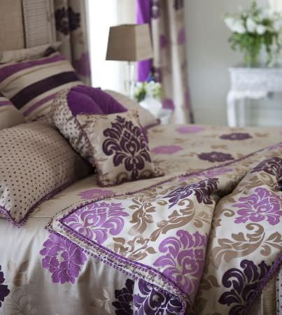 Prestigious Textiles -  Tivoli Gardens Fabric Collection - Sandy white cushions with purple stripes and spots, and a quilt with a classic floral design in pink, purple and gold