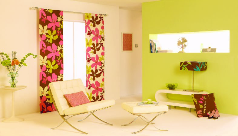 Prestigious Textiles -  Tropical Fabric Collection - A white and a brown curtain with a modern pink and green tropical flower design, and a white padded chair and footstool with a pink cushion