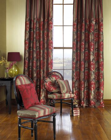 Prestigious Textiles -  Venice Fabric Collection - Brass coloured curtains with a striped top and flower decorated bottom, and antique padded chairs with red and gery stripes and red cushions