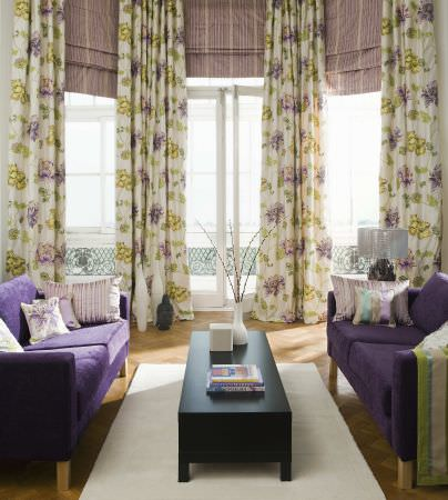 Prestigious Textiles -  West End Fabric Collection - Light yellow curtains, with bright yellow and light purple classic flower design, striped roman blinds, and white cushions with flowers