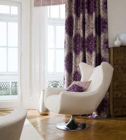 Prestigious Textiles -  West End Fabric Collection - Light purple curtain with a dark purple and white classic decorative pattern, purple cushions with stripes and patterns, and a modern chair