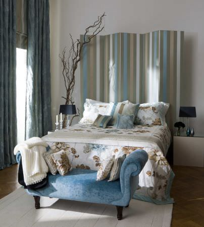 Prestigious Textiles -  West End Fabric Collection - White quilt and pillows with blue and gold detailed flower print and blue edges, small cushions, and blue curtains and roman blinds