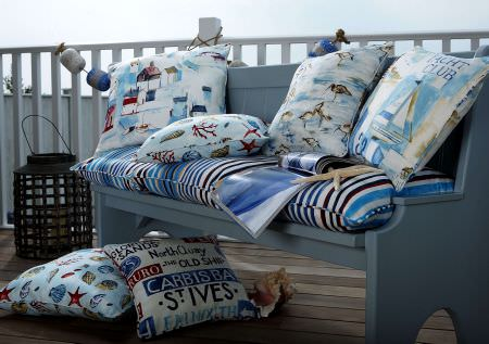 Prestigious Textiles -  Westward Ho Fabric Collection - A bench with a blue and white seating pad, and cushions with images of yachts, sea life, birds, buildings, and signs
