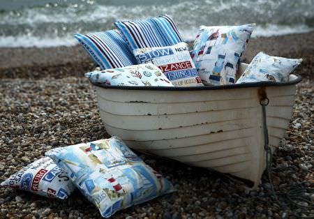 Prestigious Textiles -  Westward Ho Fabric Collection - Small boat with a blue and white striped cushion, a cushion with drawings of buildings, signs, and a cushion with sea life