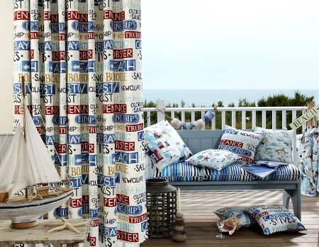 Prestigious Textiles -  Westward Ho Fabric Collection - White curtain with signs for the beach, a blue and white striped bench seating pad, and cushions with images of fish, starfish and signs