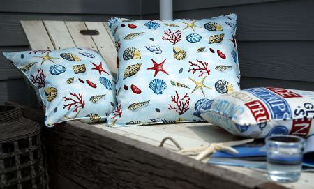 Prestigious Textiles -  Westward Ho Fabric Collection - Light blue pillows with drawings of starfish and shellfish, and a white cushion with signs from the Westward Ho fabric collection
