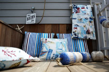Prestigious Textiles -  Westward Ho Fabric Collection - A blue and white striped seating pad, a white and blue pillow with images of ships. and a cushion with pictures of starfish and seashells