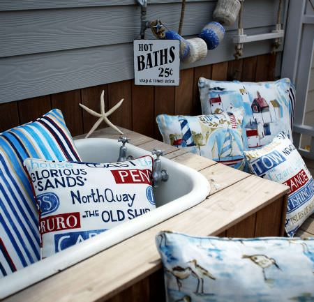 Prestigious Textiles -  Westward Ho Fabric Collection - A blue and white striped cushion, cushions with images of buildings and yachts, a cushion with signs and a cushion with birds