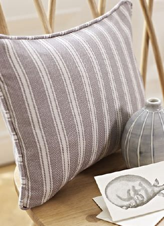 Prestigious Textiles -  Windermere Fabric Collection - A simple wood chair with a white and grey card, a small round grey vase, and a grey cushion featuring simple white stripes