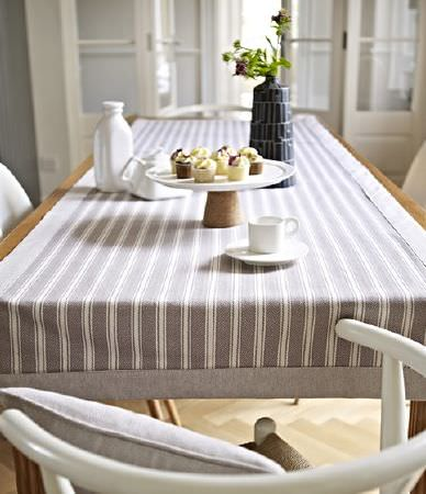 Prestigious Textiles -  Windermere Fabric Collection - Simple curved white chairs around a table with a wide grey and white striped table runner, with a cake stand and crockery