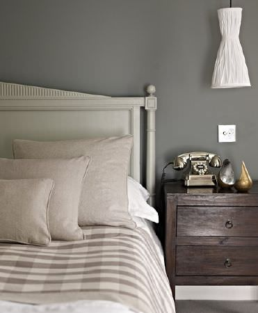 Prestigious Textiles -  Windermere Fabric Collection - A dark wood side table beside an off-white wood framed bed with plain beige cushions and a beige and cream checked duvet