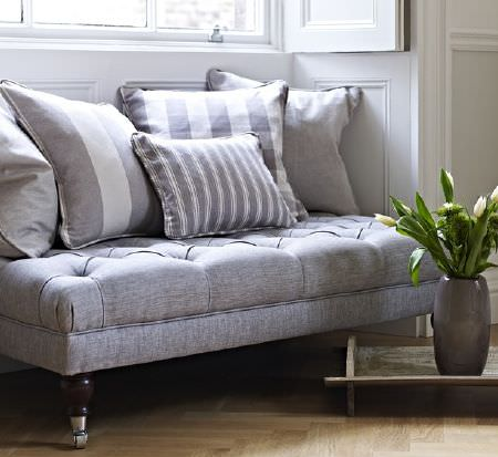Prestigious Textiles -  Windermere Fabric Collection - A window seat made from a large, low, padded footstool in light grey, with five grey and white striped scatter cushions