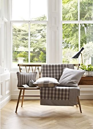 Prestigious Textiles -  Windermere Fabric Collection - Three cushions and a checked throw, all in iron grey and white, draped on a simple sofa made from wood, with a black lamp