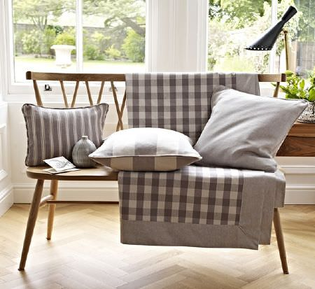 Prestigious Textiles -  Windermere Fabric Collection - A simple wooden chair with grey and white fabrics made into a checked throw and three plain and striped cushions