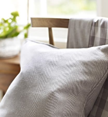 Prestigious Textiles -  Windermere Fabric Collection - A simple wooden chair with a throw made from grey and white checked fabric, with a herringbone print light grey cushion