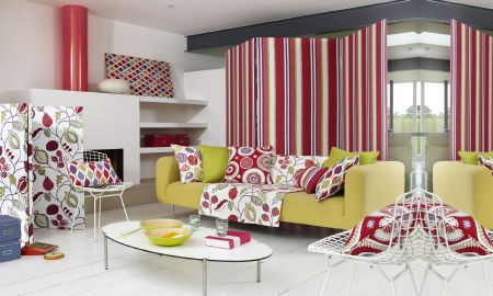 Prestigious Textiles -  Zest Fabric Collection - Bright and modern lounge area with green sofa, large print leaf motif throw and bright cushions in red, pink and green