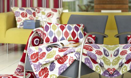 Prestigious Textiles -  Zest Fabric Collection - Vibrant leaf design throw in red, purple, white and gree, matching cushions in geometric designs