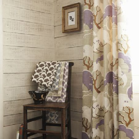 Rapture and Wright -  Rapture and Wright Collection - Mauve, light grey, white and brown tree print curtains, a dark wood chair draped with folds of fabric, and a black bowl
