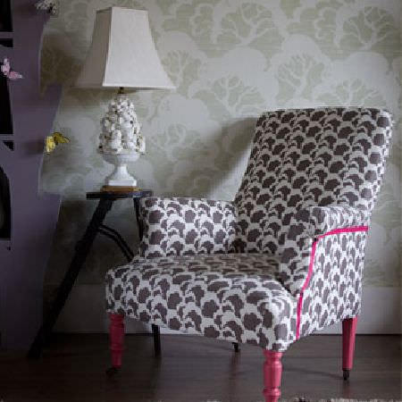 Rapture and Wright -  Rapture and Wright Collection - A grey and white cloud print armchair with painted candy pink feet, a small dark wood table and an ornate white lamp