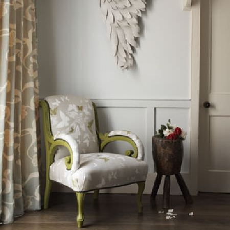 Rapture and Wright -  Rapture and Wright Collection - Butterfly prints on a pale grey and white armchair with an olive green frame and curving arms, with patterned curtains