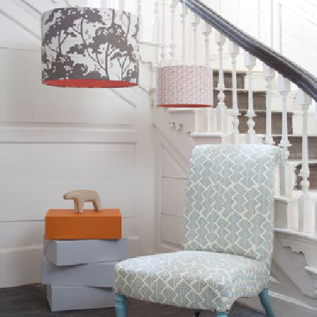 Rapture and Wright -  Rapture and Wright Collection - Two red, grey and white patterned ceiling light shades, a pale grey and white patterned chair, and orange and pale blue boxes