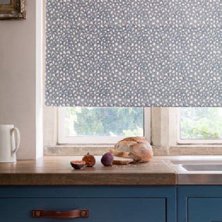 Rapture and Wright -  Rapture and Wright Collection - Dusky blue kitchen cabinets with a brown wood surface, beneath a window with a blue and white patterned roller blind