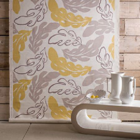 Rapture and Wright -  Rapture and Wright Collection - A roll of white fabric featuring a large yellow and grey oak leaf print, with a modern curved white table and white jugs