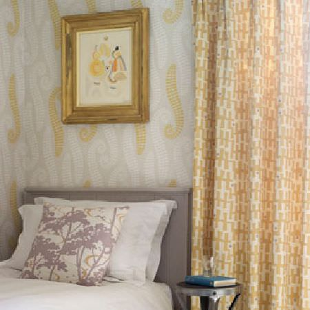 Rapture and Wright -  Rapture and Wright Collection - Caramel and white patterned curtains, grey, gold and white patterned walls, a grey headboard behind white sheets and a cushion